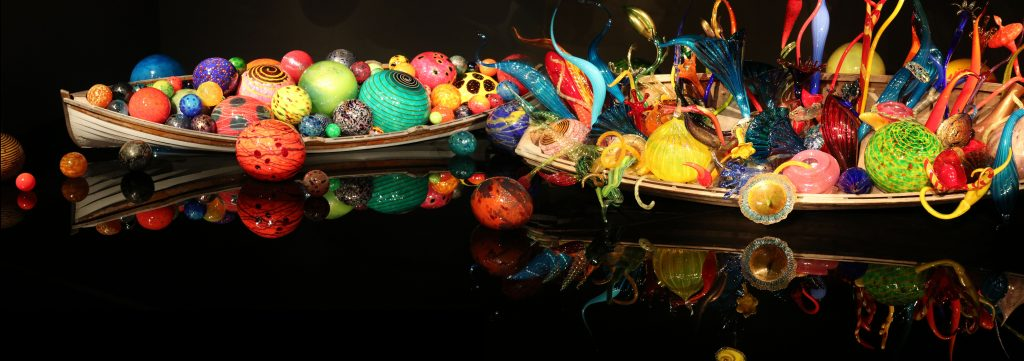 Multicolored blown-glass balls and curvy flute-shapes vases in wooden boats on a mirrored glass floor.